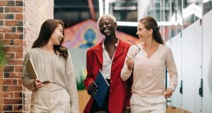 diverse successful businesswomen smiling and walking together in modern workplace